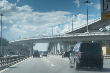 New Riga highway. Elevated roads on cloudy day. City traffic with a lot of cars.