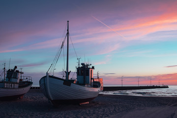 Cute small fishing boats lying on the danish beach at colorful sunset creating a perfect scandinavian summer vacation memory. Løkken in North Jutland in Denmark, Skagerrak, North Sea