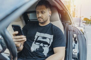 Close up of man sitting in the black car and looking at mobile phone screen.