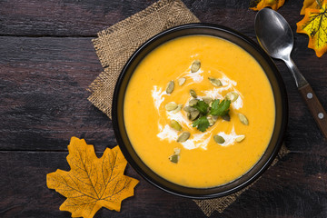 Pumpkin cream soup on dark wooden table.