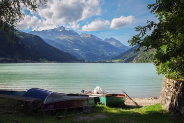 Boats are lying on the shore of Lago di Poschiavo (Graubunden, Switzerland).Poschiavo's only direct connection to Engadin and the rest of Switzerland is over the Bernina Pass.