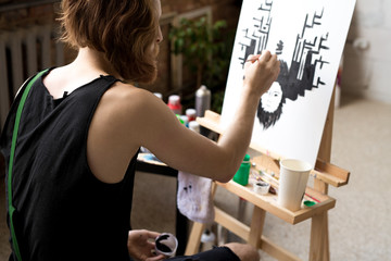 Back view portrait of long haired contemporary artist painting picture on easel in black ink while enjoying work in art studio