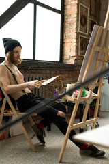 Full length portrait of handsome contemporary artist drawing sketches while sitting by easel in loft like art studio