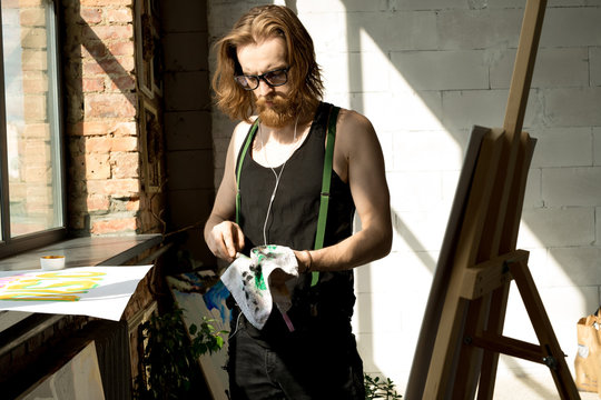 Waist up portrait of contemporary long-haired artist wiping brushes while painting by easel in art studio , copy space