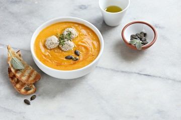 Pumpkin soup with meat balls and pumpkin seeds topping. Copy space