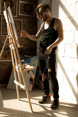 Full length  portrait of handsome male artist painting picture on easel in art studio lit by sunlight, copy space