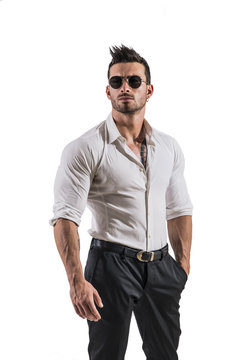 Portrait of brunette young man in white shirt and sunglasses, standing in studio shot isolated against white background. Full length photo