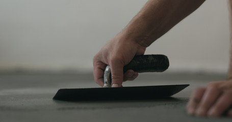 closeup worker applying micro concrete on the floor with a trowel