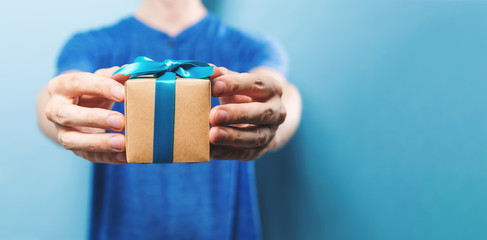 Man holding a gift box on a blue background
