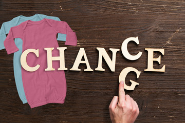 """word """"change"""" with baby clothes on wooden background"""
