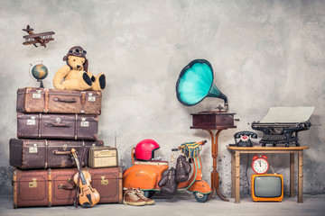Retro Teddy Bear toy in aviator's hat, wooden plane, aged classic travel valises, globe, children pedal scooter, phonograph, typewriter, clock, TV, radio, old telephone. Vintage style filtered photo