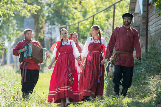 A group of young people in Russian national costumes walking around the village