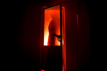 Silhouette of an unknown shadow figure on a door through a closed glass door. The silhouette of a human in front of a window at night. Scary scene halloween concept
