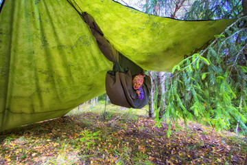 Camping in a hammock. Little girl is resting in a camouflage hammock in a forest. Travel and adventure