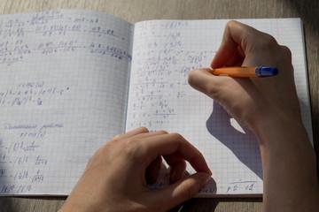 A female hand writes mathematical formulas in a notebook. School homework in mathematics