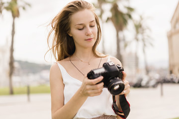 Professional female photographer taking pictures on a modern dslr camera in the park while walking around in the fresh air, young traveller girl using photo camera and shooting landscapes