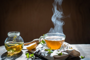 Photo sur Aluminium The Hot tea in glass teapot and cup with steam on wood background