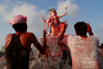 Devotees splash water on an idol of Hindu elephant god Ganesh, the deity of prosperity, as it is carried for immersion into the Arabian Sea on the last day of the Ganesh Chaturthi festival in Mumbai