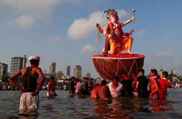 Devotees pull an idol of Hindu elephant god Ganesh, the deity of prosperity, as it is carried for immersion into the Arabian Sea on the last day of the Ganesh Chaturthi festival in Mumbai