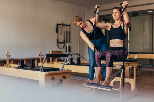 Woman training on stretch bands sitting at a gym