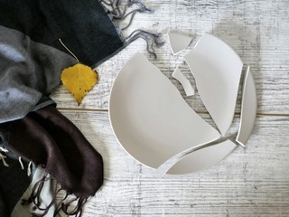 Broken plate on a light wooden table, gray napkin, top view