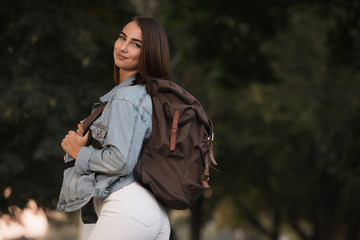 Woman in autumn season clothes with backpack at the park