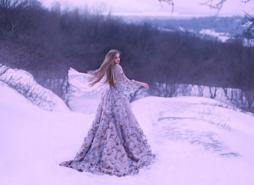 a young girl with straight fair hair in a light flying flying in the wind a purple lilac long dress decorated with flowers stands on a hill in winter on snow in the forest. art photo in cold colors.