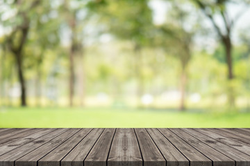Empty wood table on blurred background copy space for montage your product or design, Blank brown board with abstract blurred background at garden