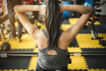 female athlete straining back muscles and arms, do sport in the fitness club