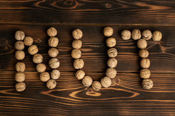The inscription Nut made of walnuts on a wooden background