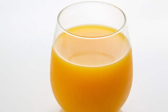 Fresh squeezed orange juice right off a tree into the glass on white kitchen table ready for breakfast in the morning