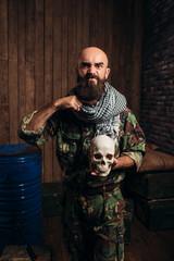 Terrorist in uniform holds human skull in hands