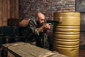 Bearded terrorist in uniform aiming from a gun