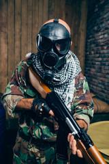 Terrorist in gas mask with kalashnikov rifle