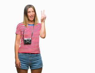 Young beautiful woman taking pictures using vintage photo camera over isolated background smiling with happy face winking at the camera doing victory sign. Number two.