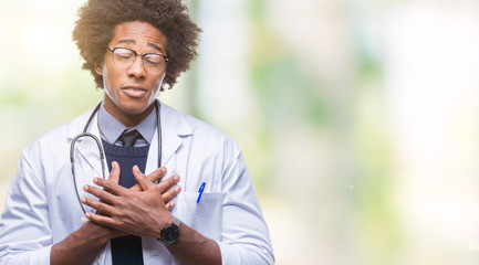 Afro american doctor man over isolated background smiling with hands on chest with closed eyes and grateful gesture on face. Health concept.