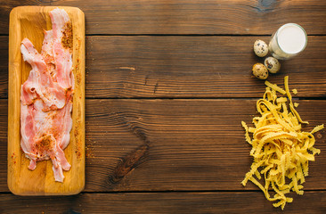Raw meat, pasta and eggs on wooden table