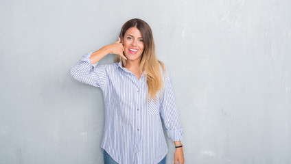Young adult woman over grey grunge wall wearing fashion business outfit smiling doing phone gesture with hand and fingers like talking on the telephone. Communicating concepts.