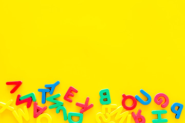 Alphabet for kids concept. English letters in disorder on yellow background top view copy space