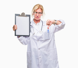 Middle age blonde doctor woman holding clipboard over isolated background with angry face, negative sign showing dislike with thumbs down, rejection concept