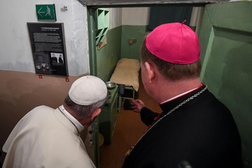 Pope Francis observes a prison cell during a visit at the Museum of Occupations and Freedom Fights, in Vilnius