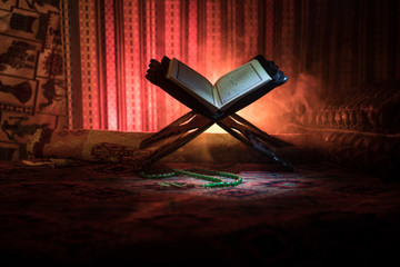 Open holy book of Muslims on stand on eastern carpet with dark toned foggy background. Muslim religion concept. Selective focus.