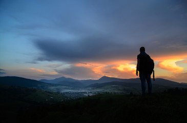 A traveler-photographer observes the sunset over the forest and mountains in the Ukrainian Carpathians