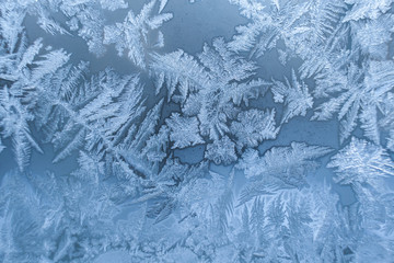 Close-up white winter window with frosty pattern as background .
