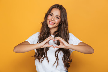 Image of charming woman 20s with long hair smiling and showing heart shape with fingers, isolated over yellow background