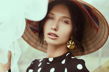 Gorgeous brunette woman in fashion dress with straw chinese hat