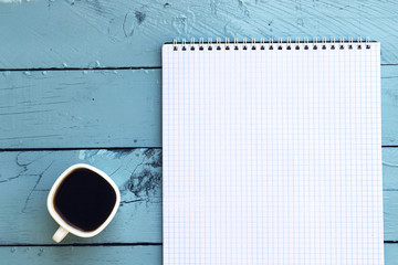 coffe cup and notebook in blue table