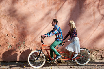Young attractive tourist couple in casual clothing, bearded man and blond woman cycling tandem bike along empty paved sunny sidewalk on background of high red crackled plastered wall.