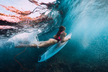 Surfer girl with surfboard dive underwater with under big wave.