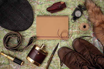 Foto auf Acrylglas Jagd Flat lay with hunting ammunition over the map as background: old boots, hat, knife, rope, belt, fox tail.